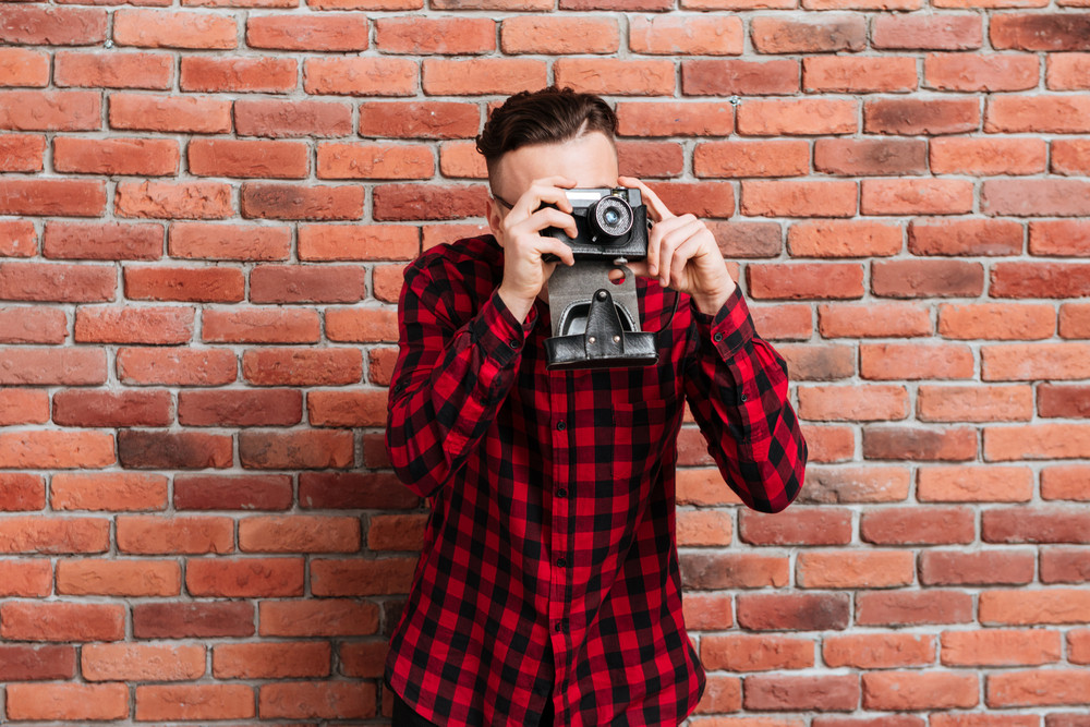 Hipster in red shirt standing near the wall and making photo on retro camera