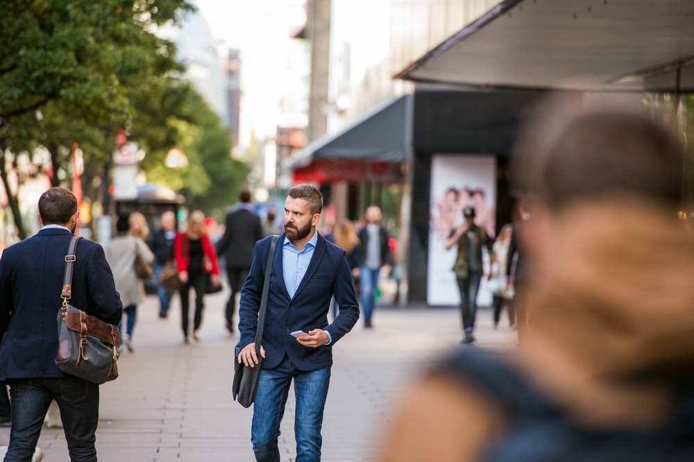 Hipster manager holding a smart phone walking in the street of London