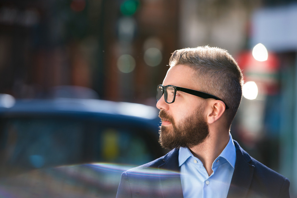Hipster manager in blue shirt and jacket walking in the street of London, wearing black eyeglasses