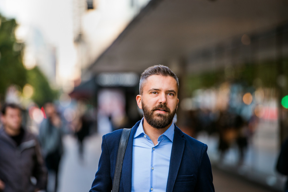 Hipster manager in blue shirt and jacket walking in the street of London