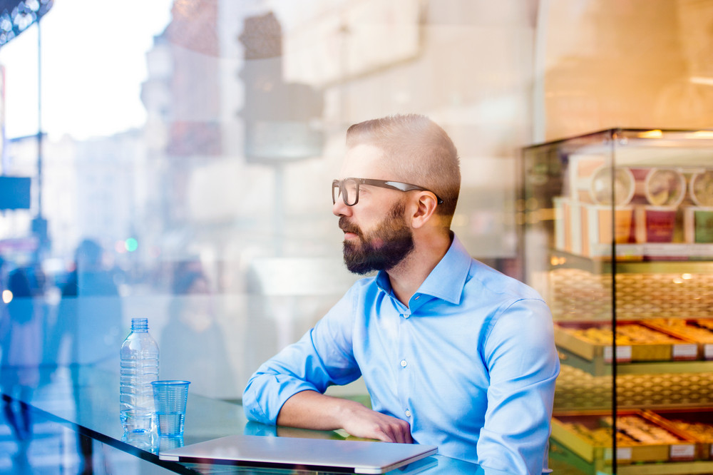 Hipster manager sitting in cafe by the window with glass of water and notebook, reflection