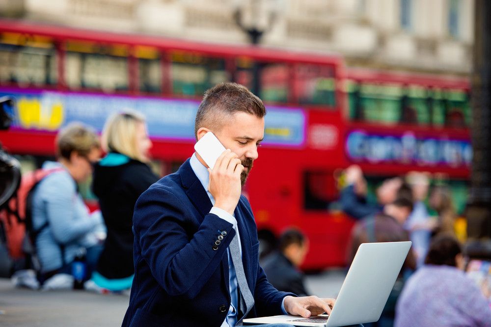 Hipster manager sitting on stairs against  Londons red double-decker buses on crowded Piccadilly Circus, working on laptop, using a smart phone