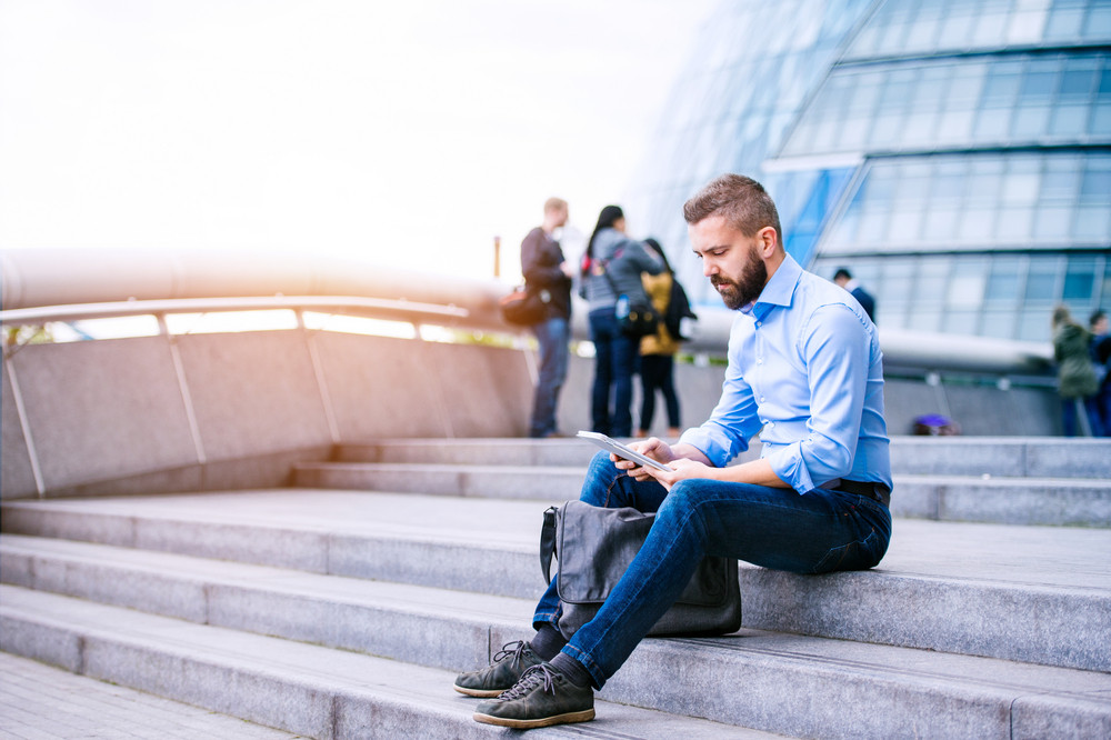 Hipster manager sitting on stairs on sunny day, working on tablet, London, City Hall