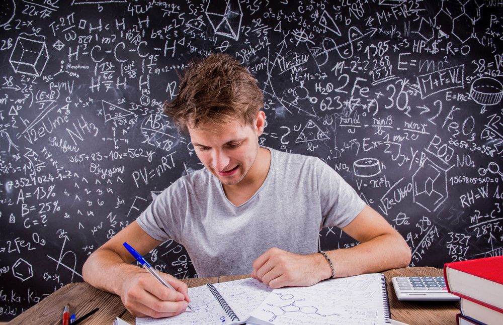 Hipster student doing his homework in front of a big blackboard