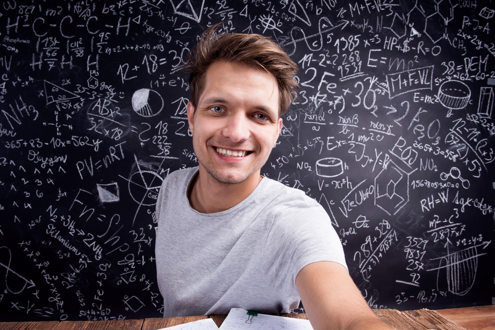 Hipster student taking selfie in front of a big blackboard