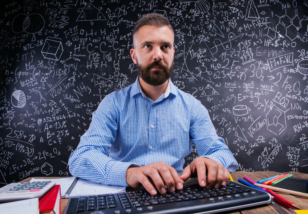 Hipster teacher sitting at the desk with various school supplies, typing on keyboard, against big blackboard with formulas and mathematical symbols