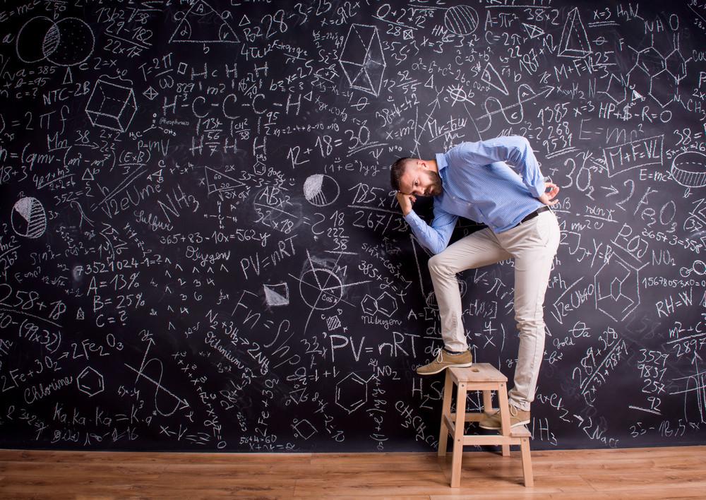 Hipster teacher standing on step ladder, against big blackboard with mathematical symbols and formulas. Studio shot on black background.