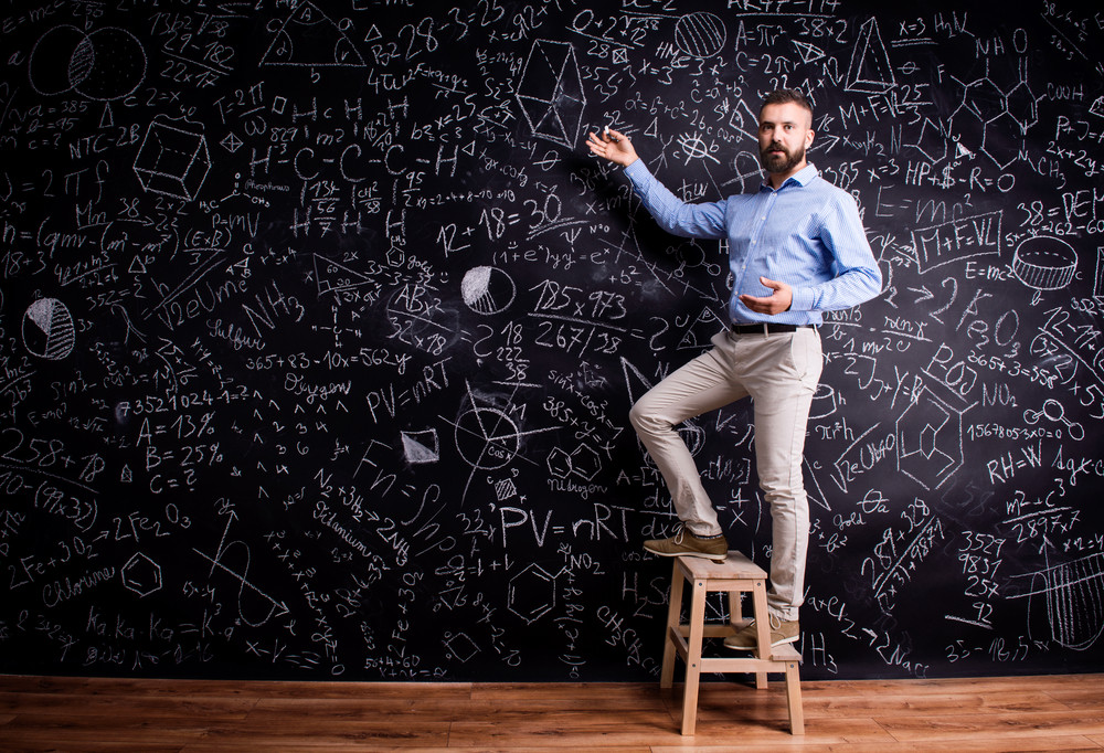 Hipster teacher writing on big blackboard with mathematical symbols and formulas, standing on step ladder. Studio shot on black background.