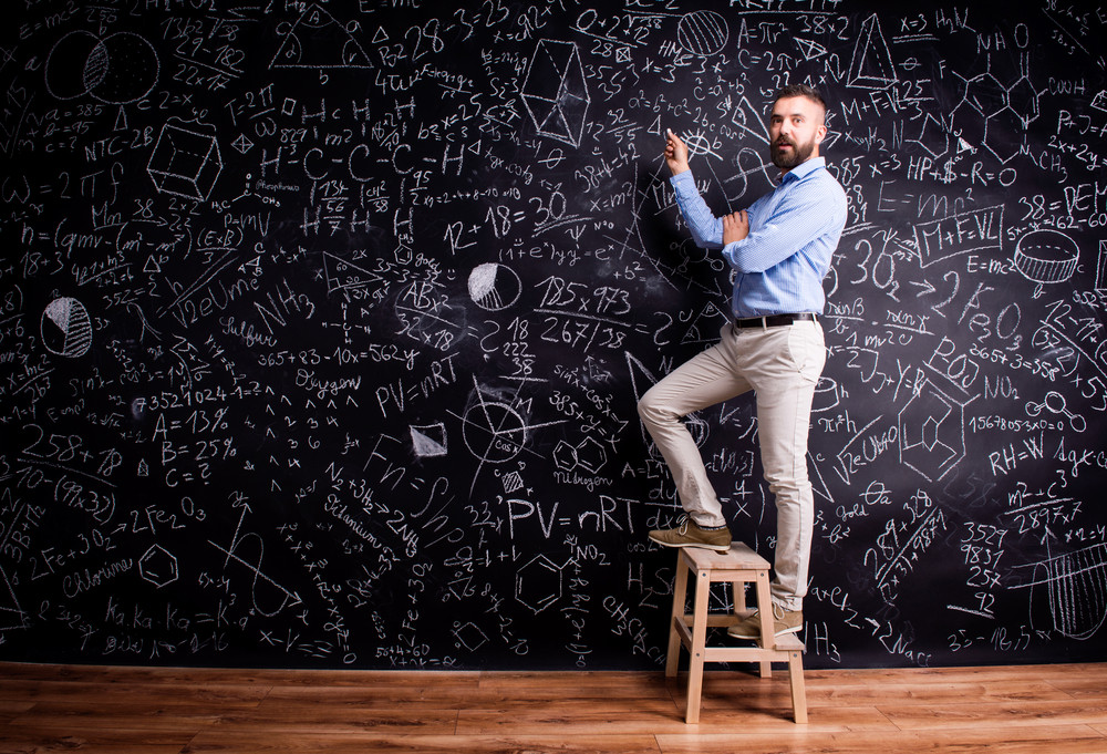 Hipster teacher writing on big blackboard with mathematical symbols and formulas, standing on step ladder. Studio shot on black background.