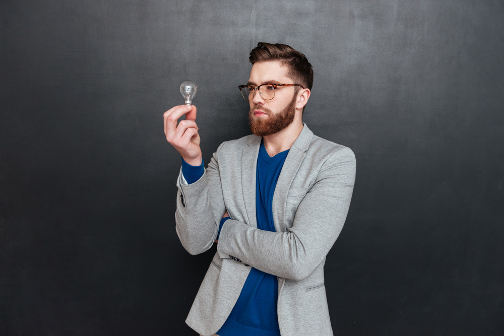 Hipster with bulb in studio. looking at bulb. isolated black background