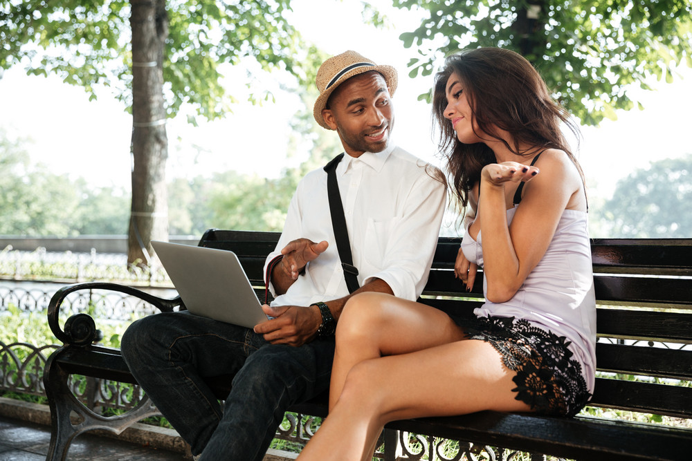 Hipster with model sitting on a bench in park. looking at laptop