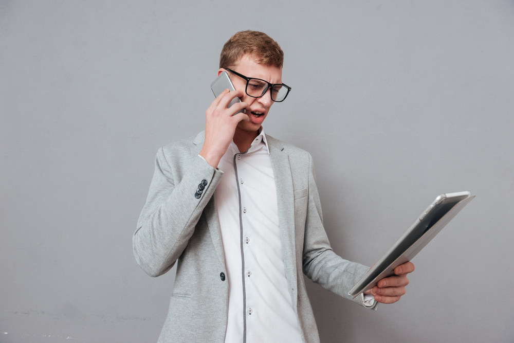 Hipster with tablet and phone in studio. isolated gray background