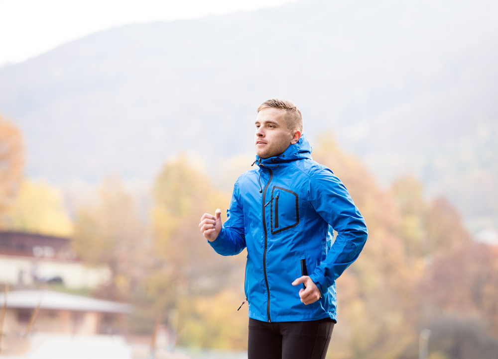 Hipster young athlete in blue jacket running outside in colorful sunny autumn nature. Trail runner training for cross country running.
