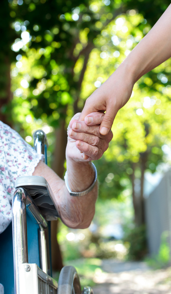 Holding hands with senior lady in wheelchair