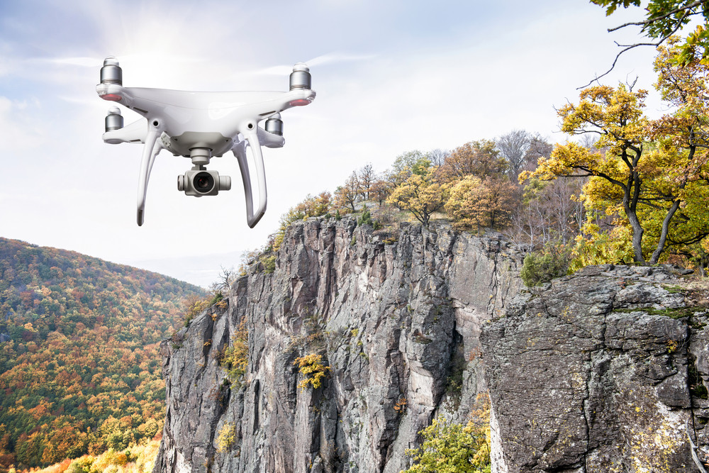 Hovering drone taking pictures of autumn nature. Colorful forest, rocky hill.