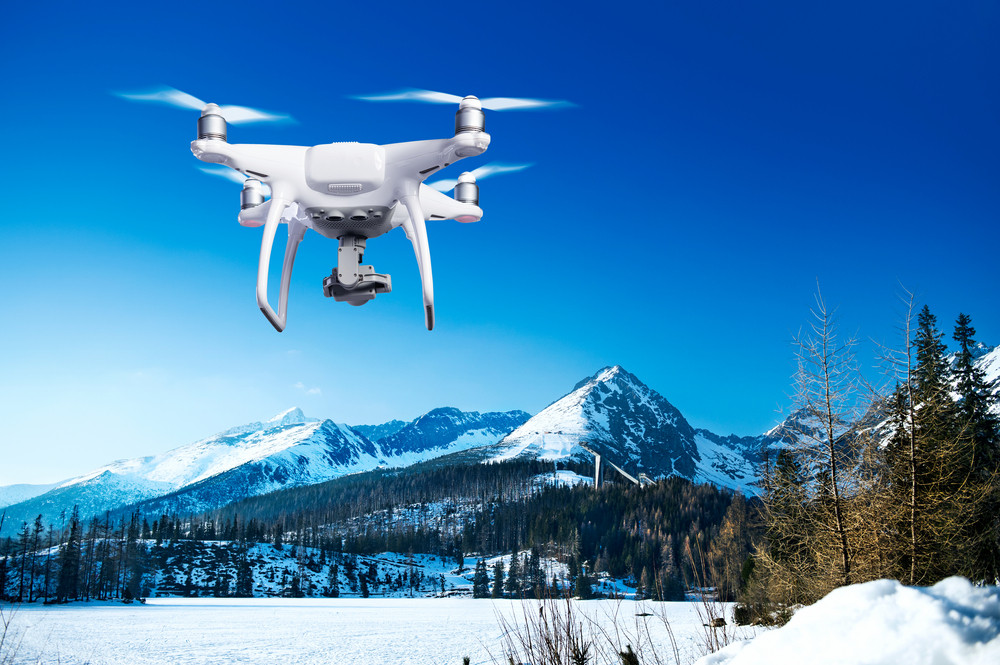 Hovering drone taking pictures of snowy white meadow, forest and mountains on sunny day with clear blue sky