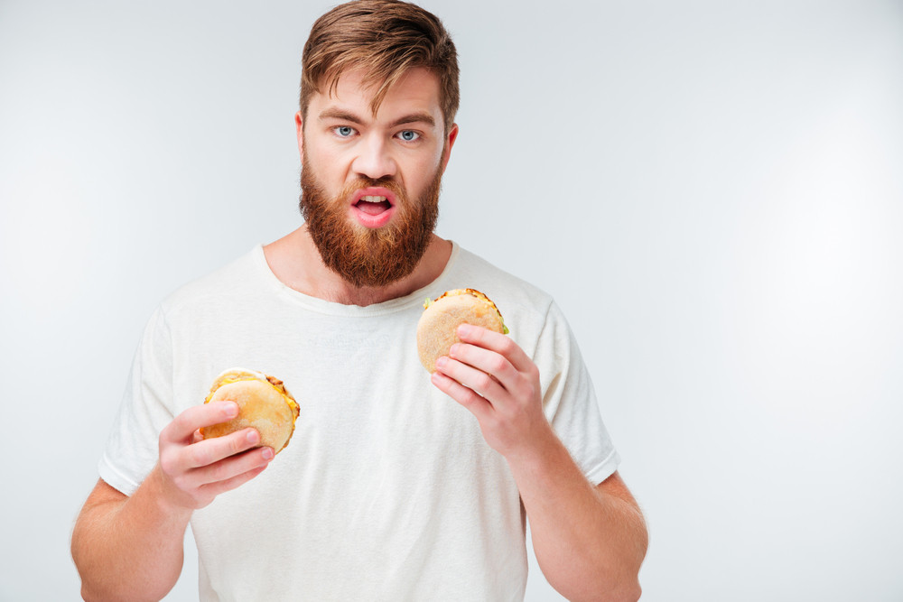 Hungry young bearded man holding two hamburgers isolated on white background