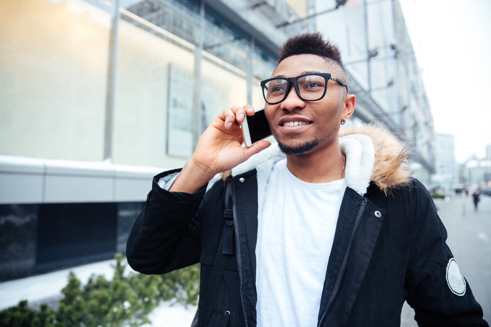 Image of a cheerful african young man walking on the street while talking by his cellphone. Looking aside.