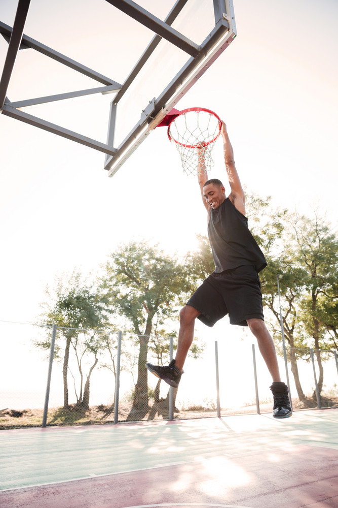 Image of african basketball player practicing for basketball. Looking at basketball hoop.