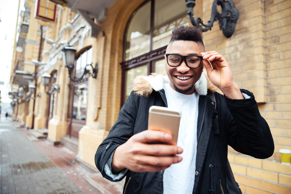 Image of african cheerful man holding his cellphone in hands and make a selfie outdoors.