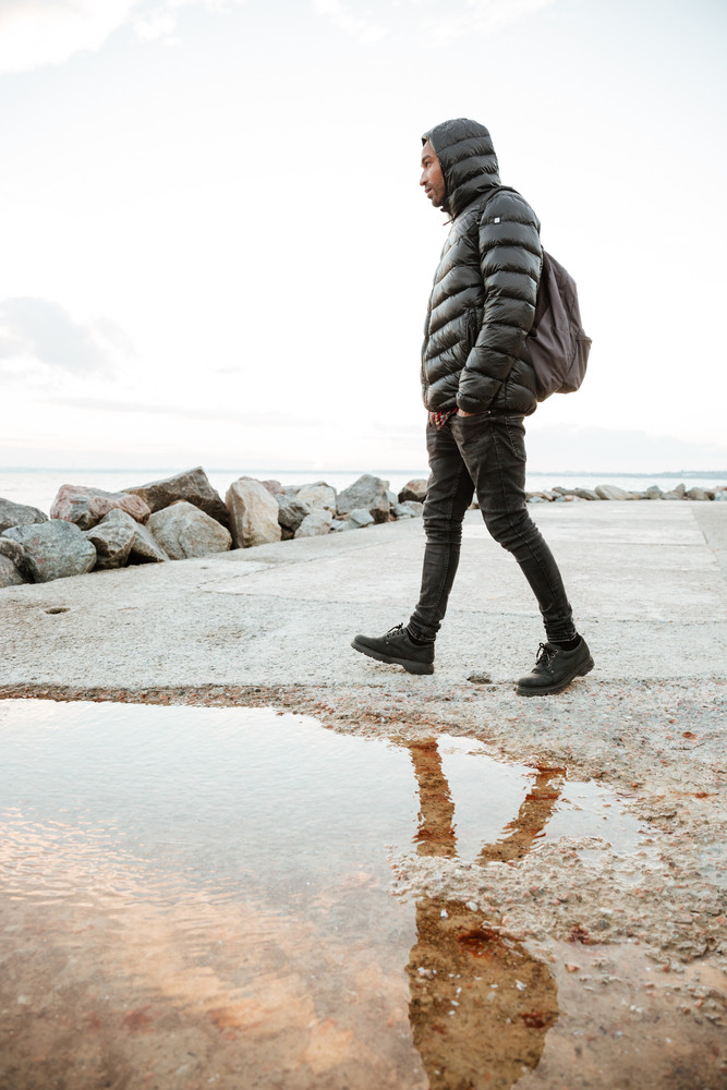 image of african concentrated man dressed in warm clothes walking on