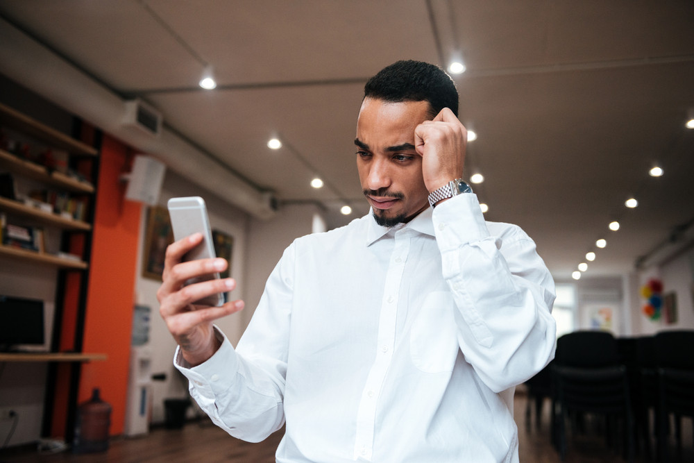 Image of african handsome businessman chatting by phone in office. Look at phone.