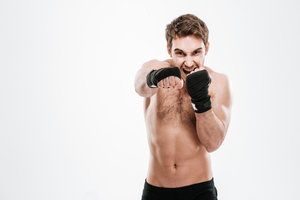 Image of agressive young man boxer make boxing exercises over white background. Look at camera.