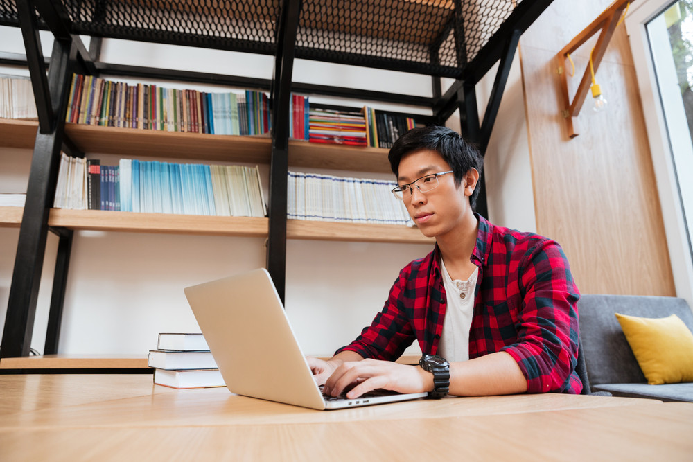 Image of asian male dressed in shirt in a cage and wearing glasses using laptop at the library. Looking at the laptop.