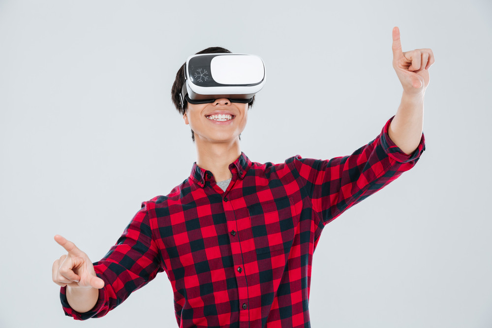Image of asian man dressed in casual shirt in a cage and wearing virtual reality device and pointing. Isolated over white background.