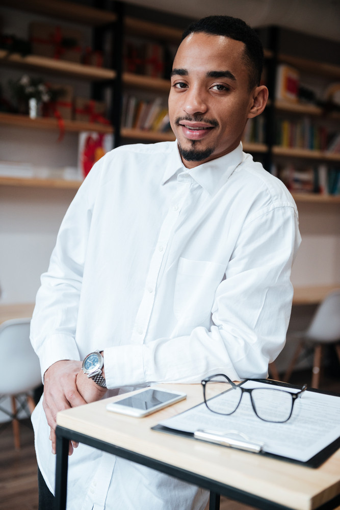 Image of attractive african businessman standing near table looking at camera. Coworking.
