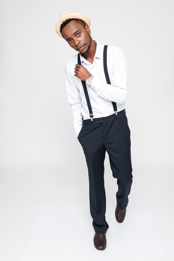 Image of attractive african man wearing hat posing in studio. Isolated over white background. Look at camera.
