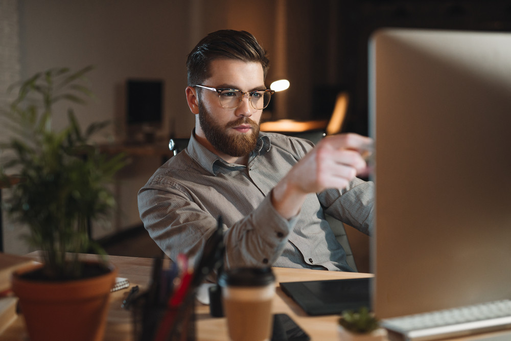 Image of attractive bearded web designer dressed in shirt working late at night and looking at computer while touching computer display