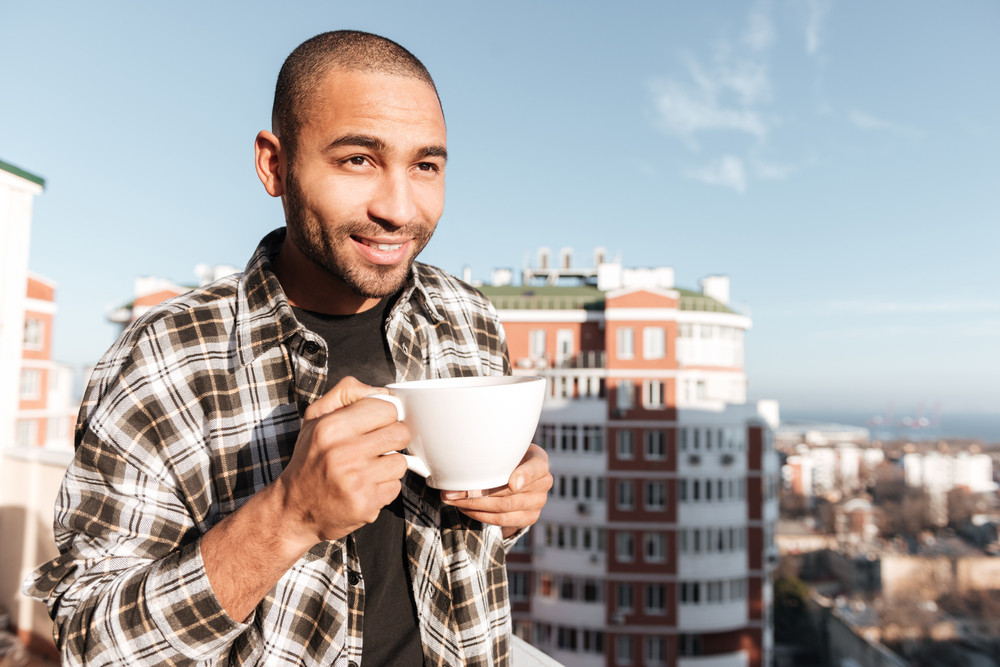 Image of attractive young african man drinking coffee while standing on roof. Look aside.
