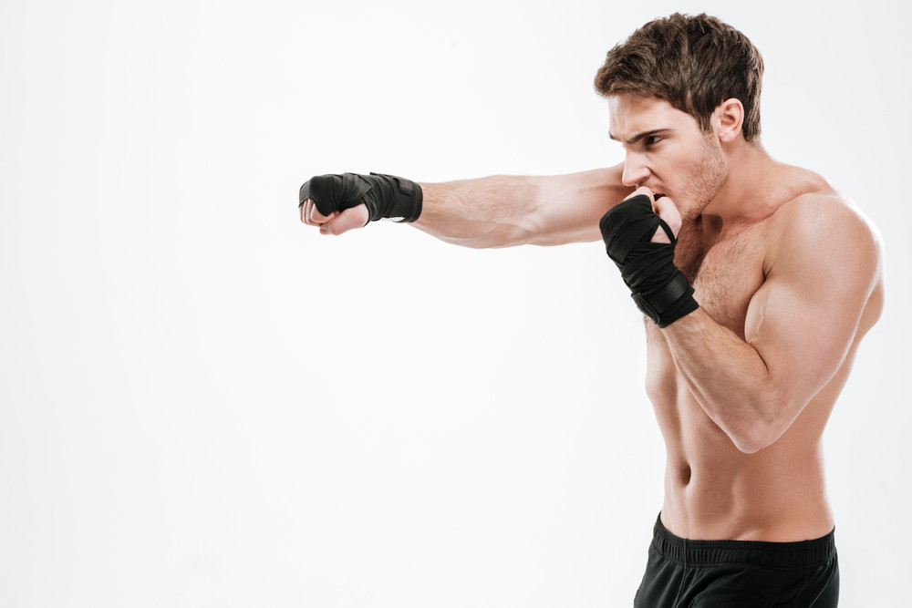 Image of attractive young man boxer make boxing exercises over white background. Look aside.