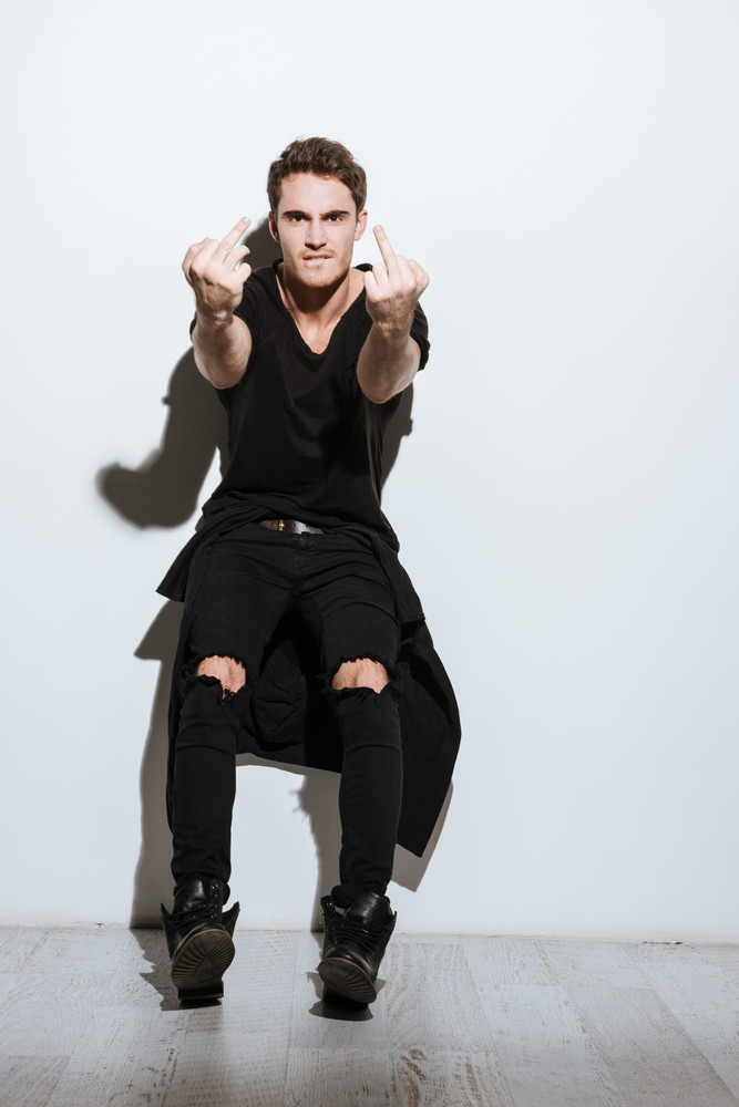 Image of attractive young man dressed in black t-shirt posing over white background showing middle finger to camera.