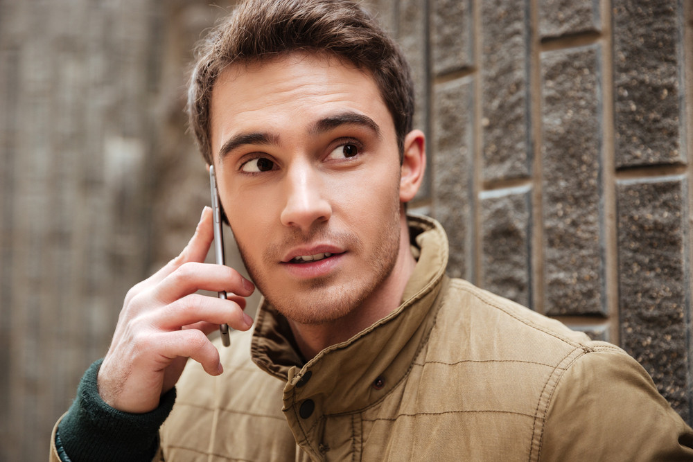 Image of attractive young man walking on the street and looking aside while talking by his phone.