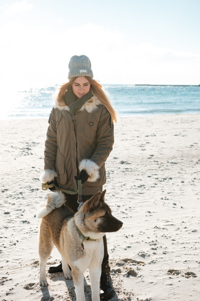Image of attractive young woman walks in winter beach with dog on a leash.