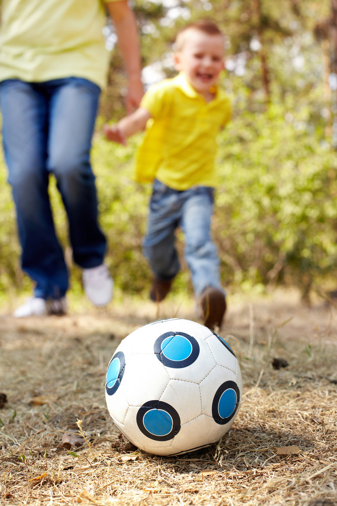 Image of ball on ground in park with child and male legs at background