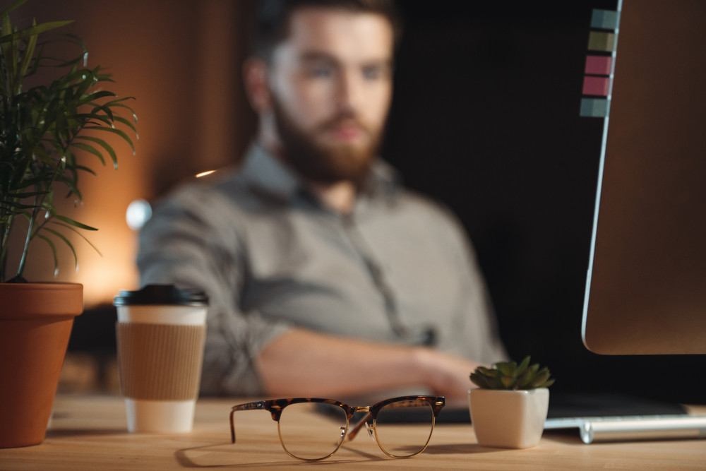 Image of bearded designer dressed in shirt in a cage working in office late at night near glasses and cup of coffee. Focus on glasses.