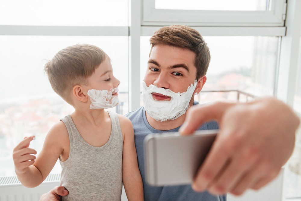 Image of bearded father and son are applying shaving foam on their faces and smiling while taking selfie.