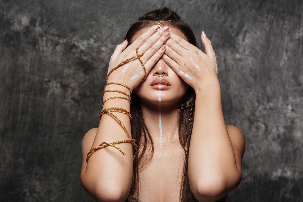 Image of beautiful asian model with bright makeup and sunburn skin covering eyes with hands.