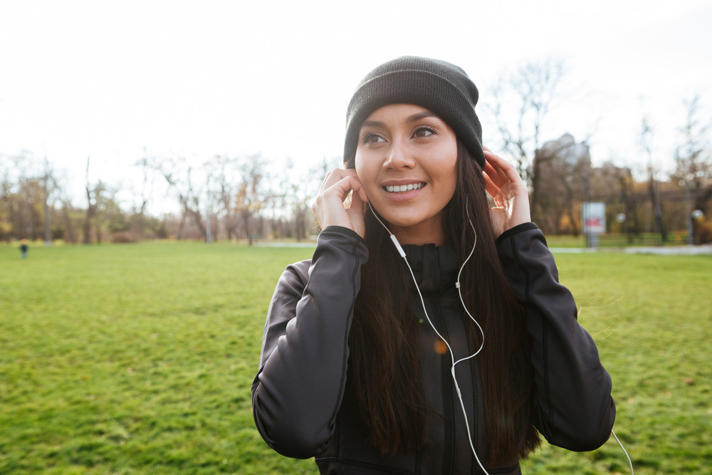 Image of beautiful lady runner in warm clothes in autumn park listening music