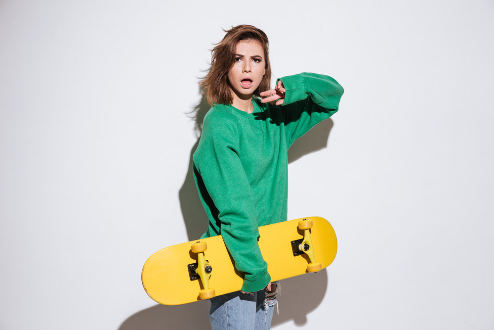 Image of beautiful skater woman dressed in green sweater standing isolated over white background with skateboard.