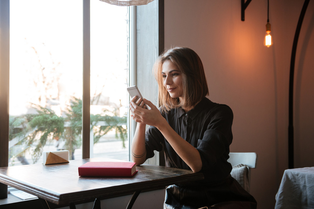 Image of beautiful young lady sitting at the table in cafe and chatting by her phone.