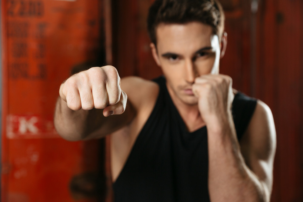 Image of boxer standing in a gym and posing with hands. Looking at camera. Focus on hands.