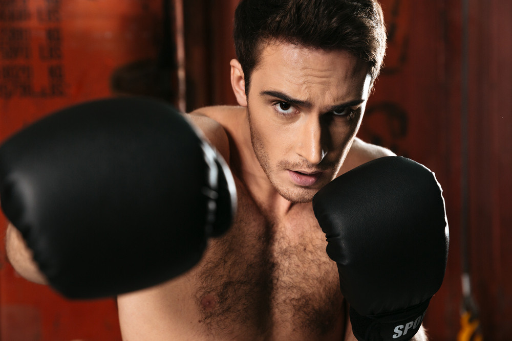 Image of boxer standing in a gym and posing with hands. Looking at camera.