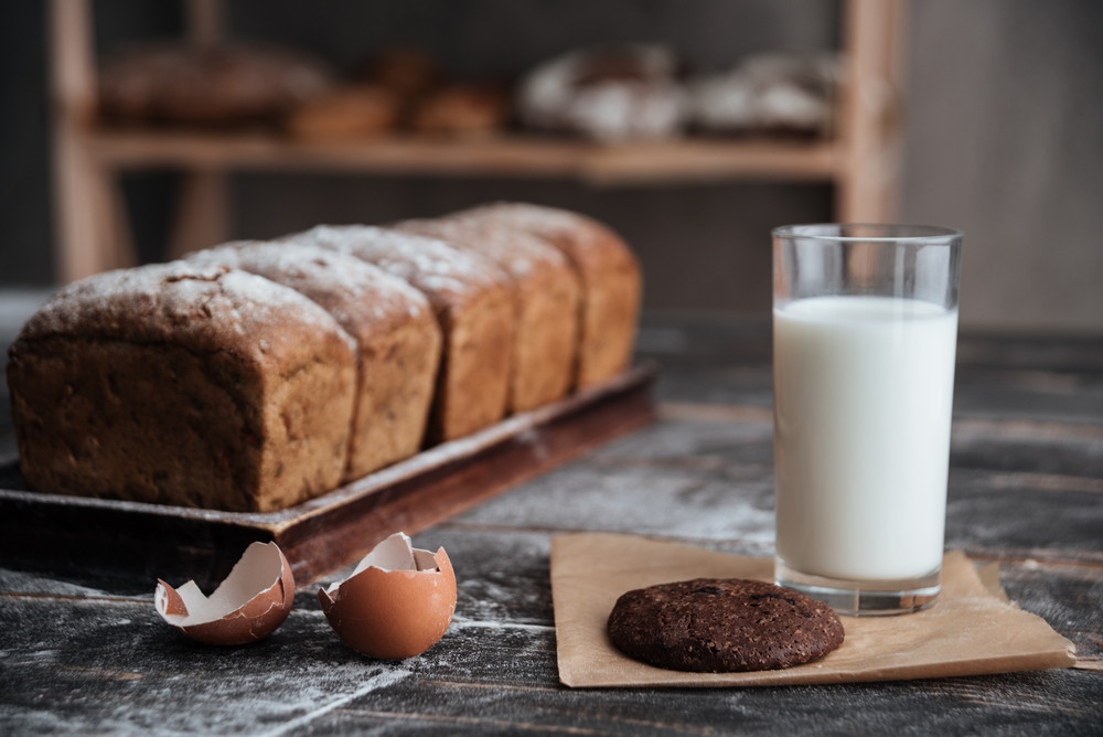 Image of bread with flour on dark wooden table with milk and cookie near eggs at bakery