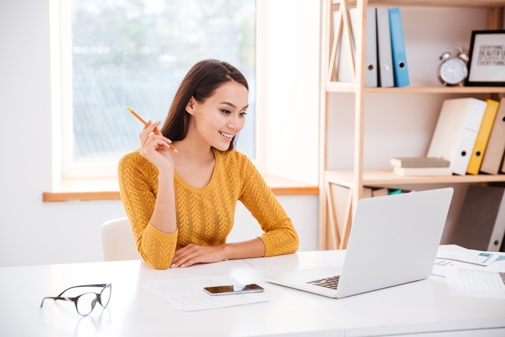 Image of cheerful businesswoman dressed in sweater sitting in office and looking at laptop.