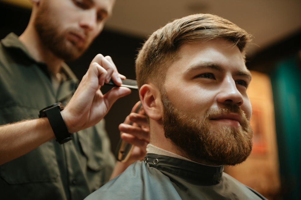 Image of cheerful man getting haircut by hairdresser with razor while sitting in chair. Look aside.
