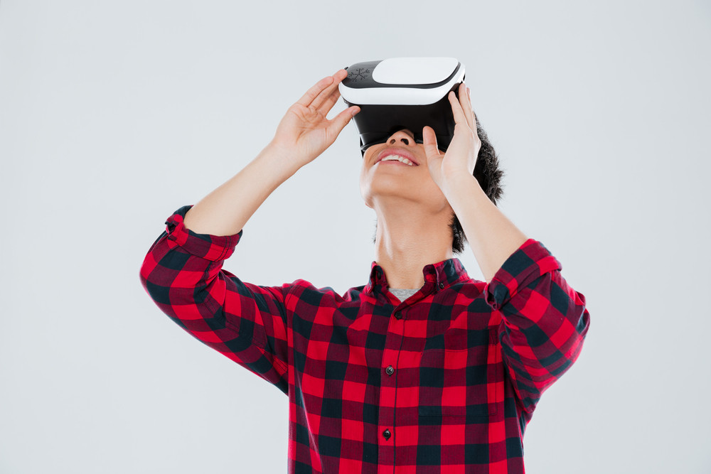 Image of cheerful young asian man dressed in casual shirt in a cage and wearing virtual reality device. Isolated over white background.